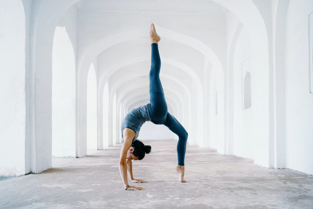 A flexible yogini doing a backbend pose in the middle of a white arc passageway. Photo by Oksana Taran.