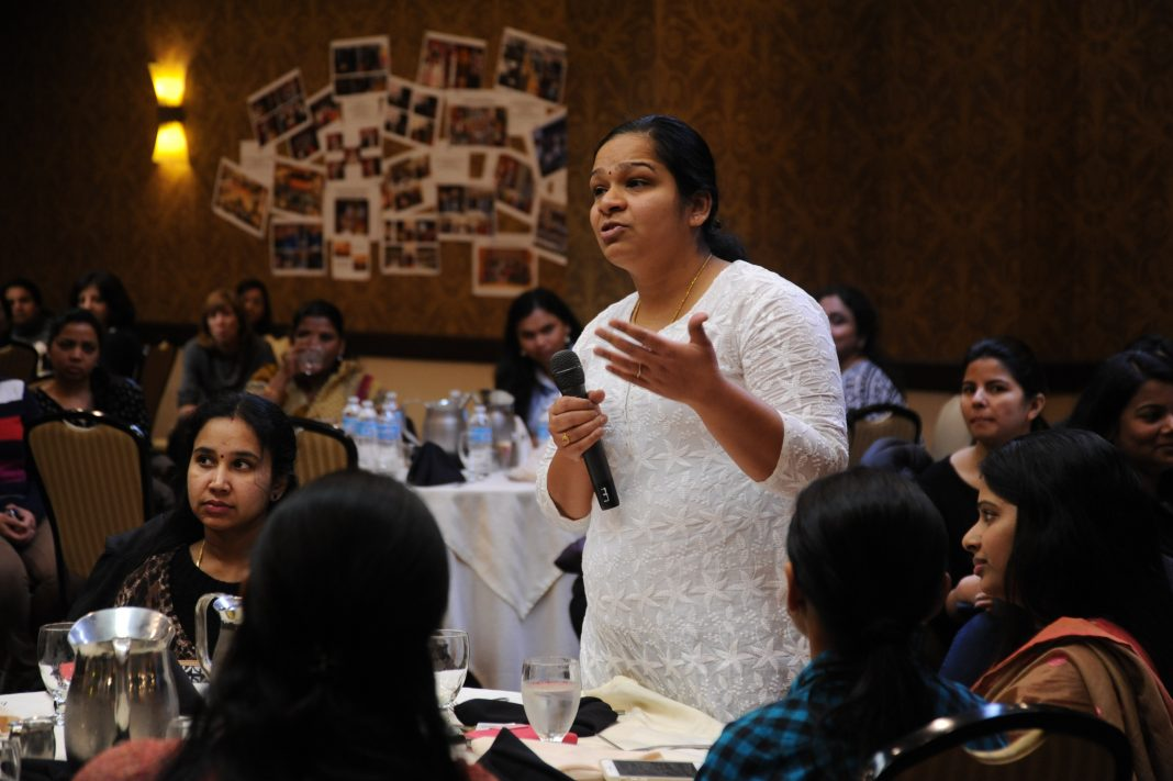 A woman advises the CEO, (out of frame), while he fields questions from the floor, A Celebration of Woman's Day, Seattle Region, Bellevue, Washington, USA. All the women shown work in high tech as consultants in the US. They are the best and brightest from universities in India. They remain concerned about children in general but specifically girls in India and the rest of the developing world and aspire to help them. Their topics deal with improving children's lives with education, fulfilling other needs. A sub-section of technology workers, many of these women are in the US on H1-B Visas.