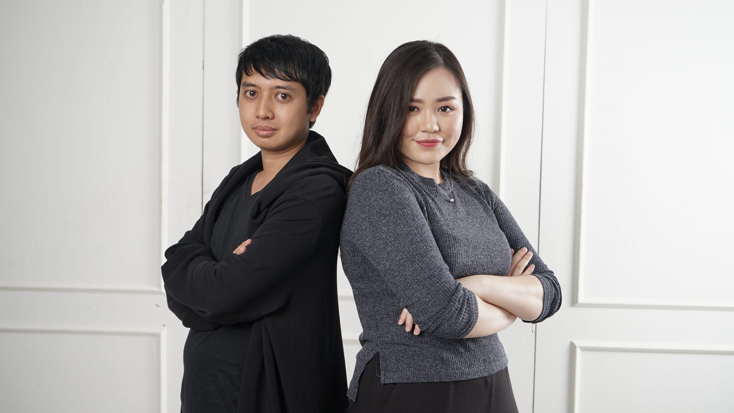 Asian Man and Asian Woman standing and smiling near white background.