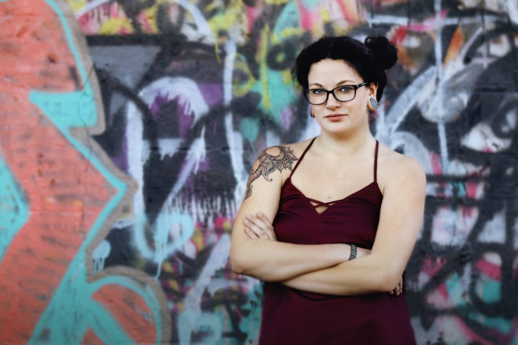 Edgy senior portrait of a young woman or girl standing with arms crossed in front of a boldly graffiti covered wall in an urban downtown location during a senior portrait session. Girl is wearing glasses with hair pulled up in messy bun, she has tattoos and body piercings as well as ear gauges. Bold, graphic colors in this female portrait of strength.