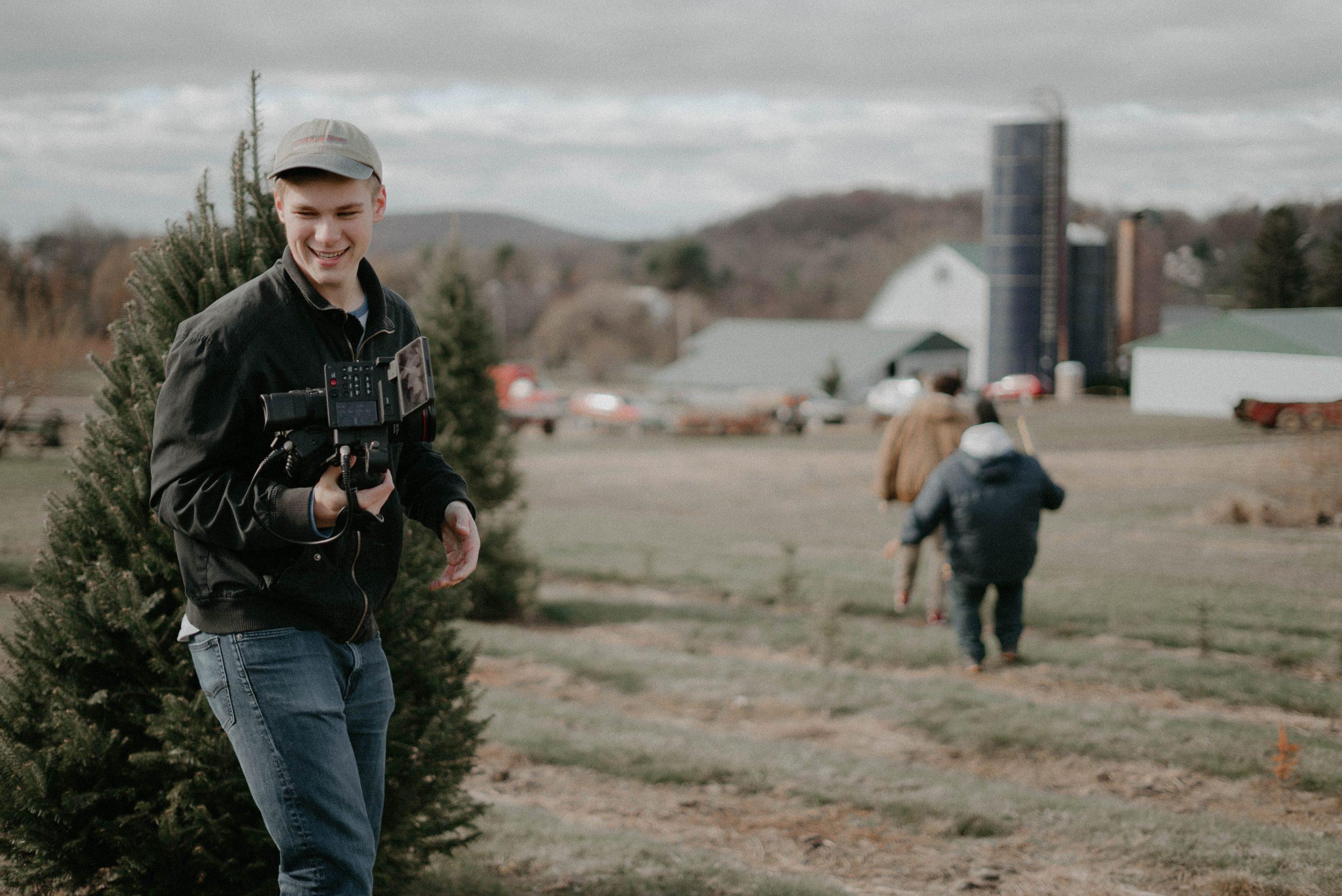 man holding video camera standing near green bush
