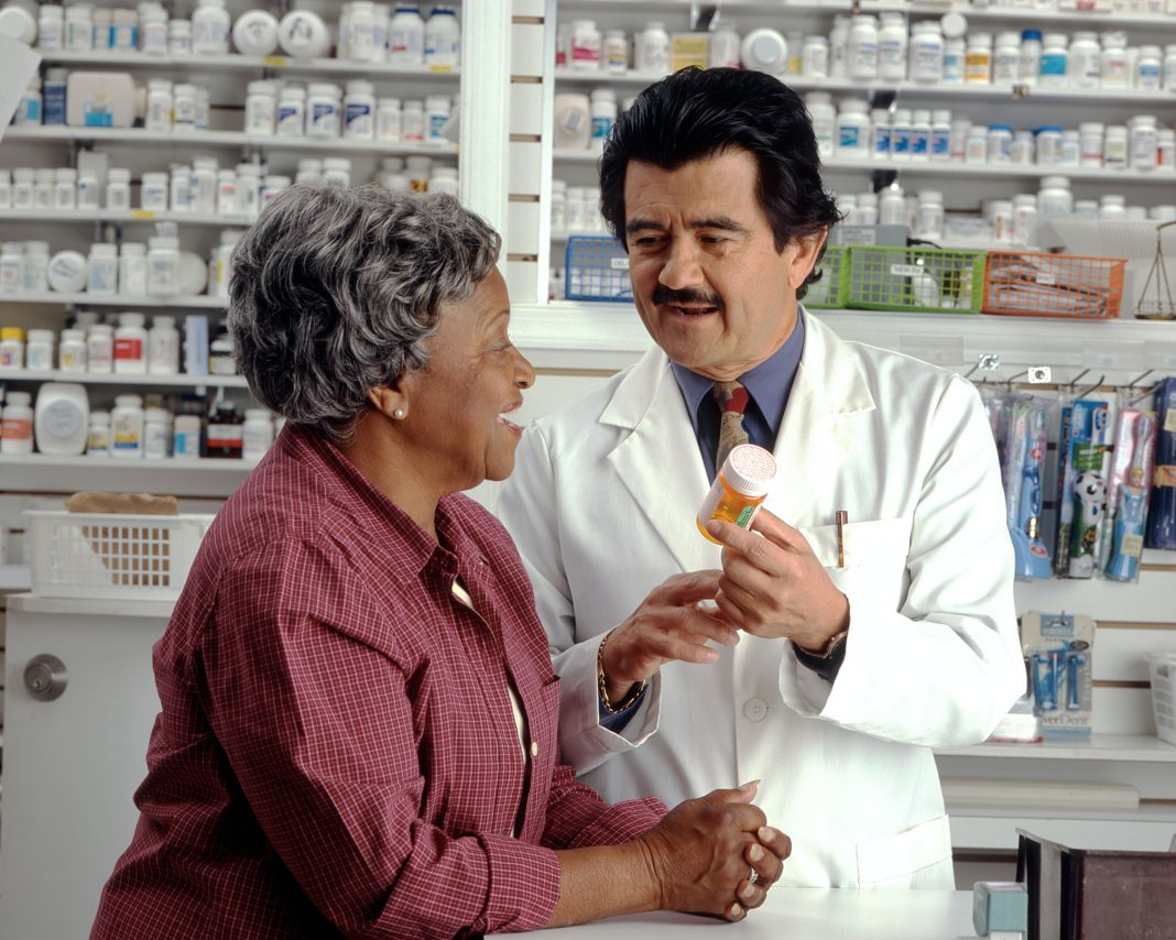 Woman Consults with Pharmacist. An older African-American woman talks to a Hispanic male pharmacist as he explains her prescription. Photographer Rhoda Baer