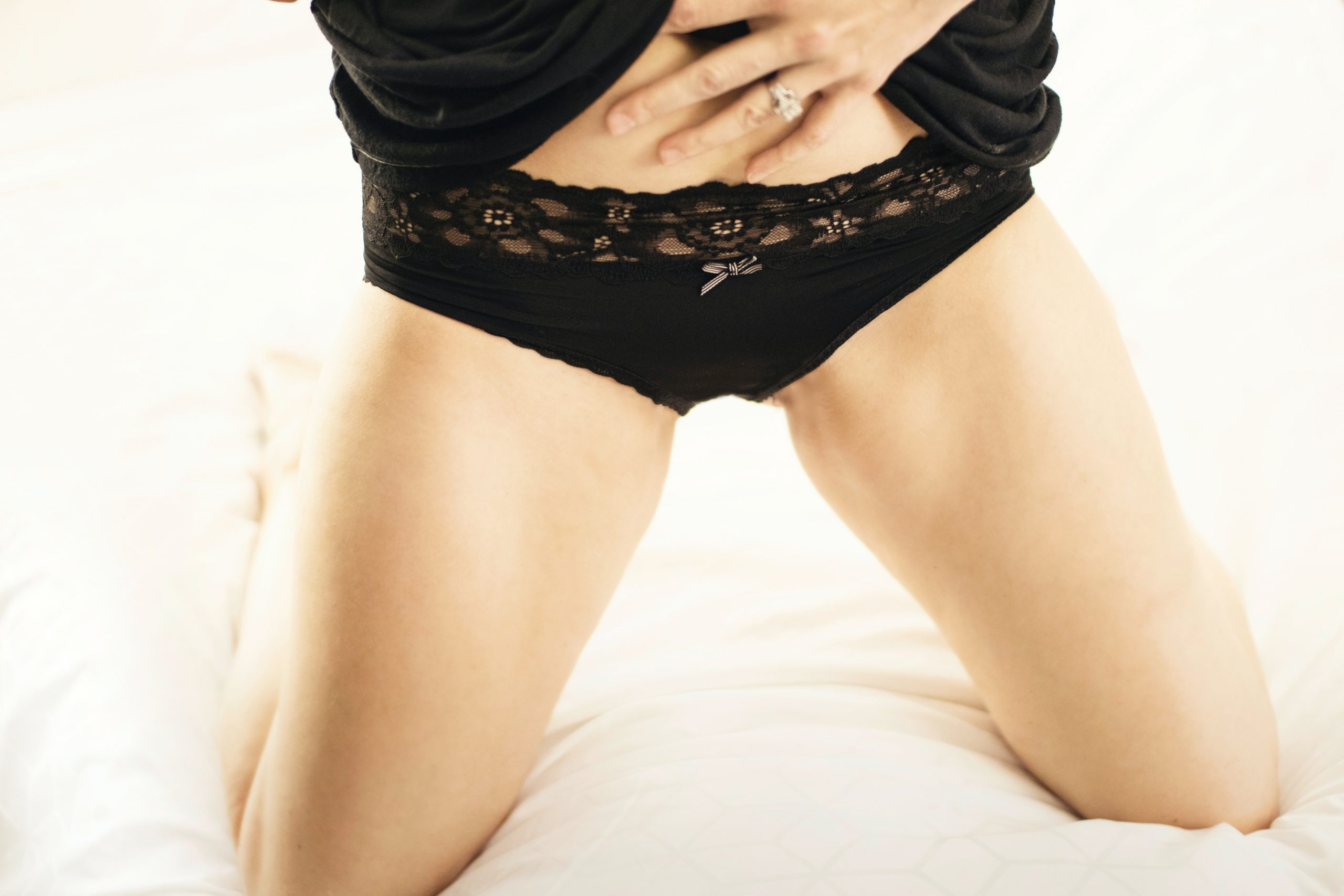 Young woman in black lacy lingerie kneeling on a white hotel bed bares her stomach, her hand teasing the waistband of her underwear against her flat stomach.